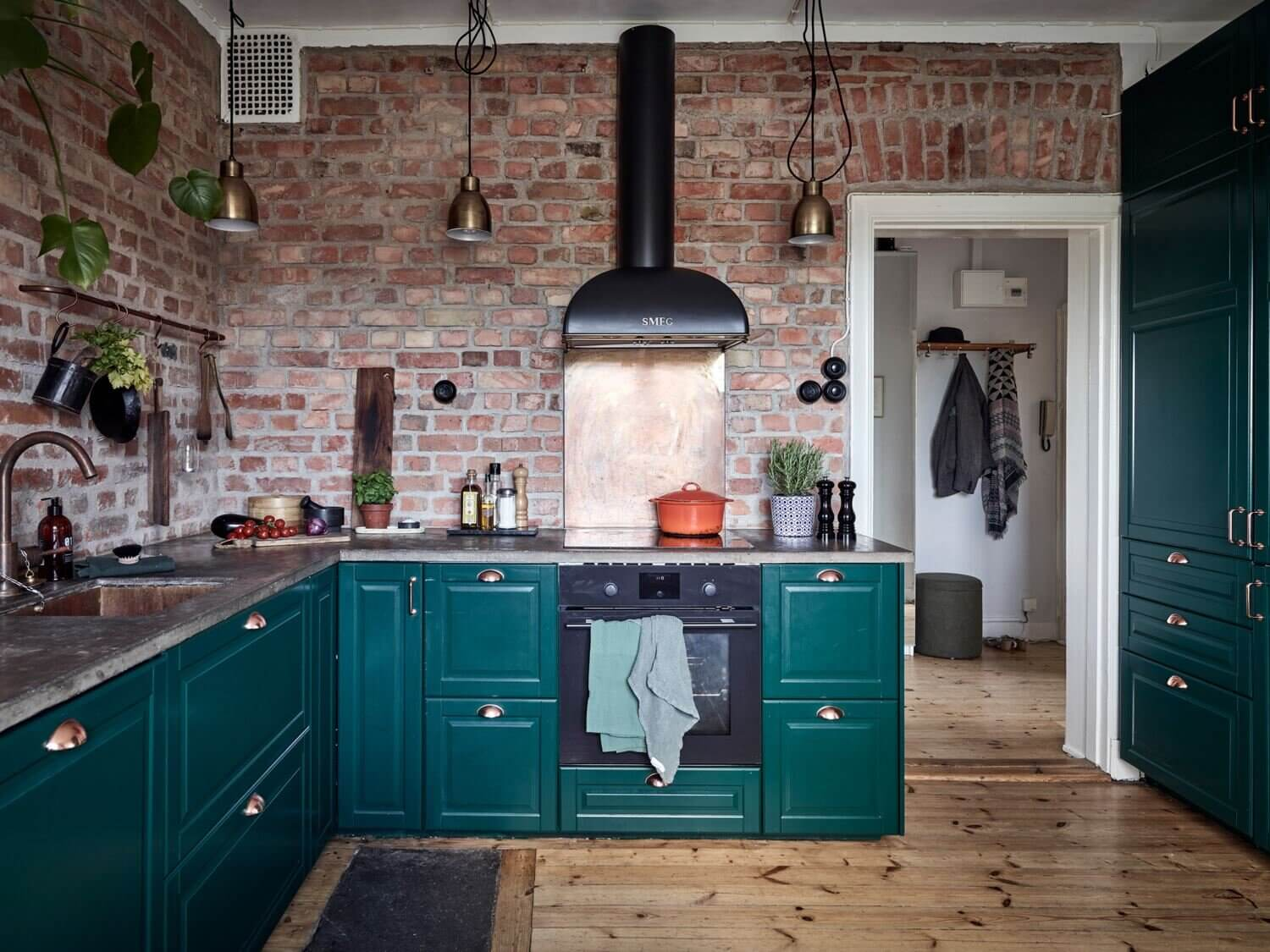 A Green Kitchen with Exposed Brick in a Scandi Apartment