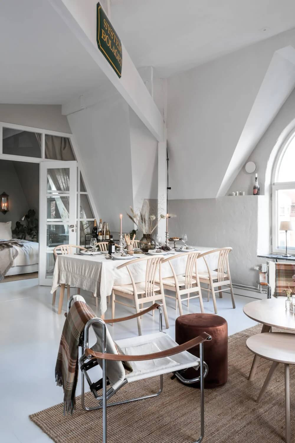 An Attic Apartment Turned Bright with White Paint and Glass Walls